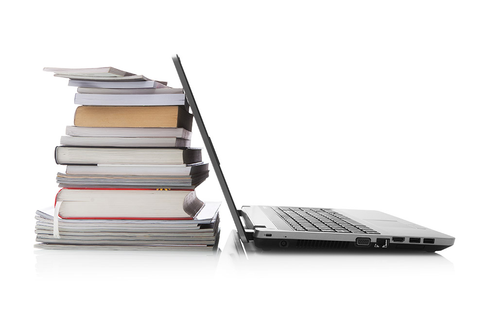 Laptop leaning against pile of books